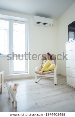 Red-haired girl in bright clothes and barefoot sits in a chair with a phone in her hands under the air conditioner. Young woman sitting in an armchair with a cat #1394403488