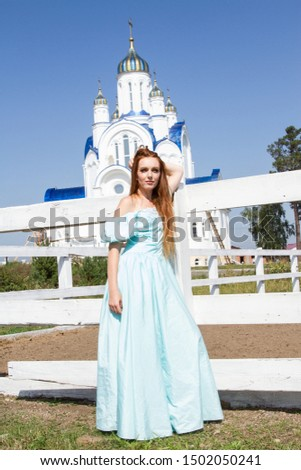 Red-haired girl in evening dress posing on the background of the Orthodox church. #1502050241
