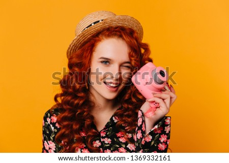 Red-haired girl in floral print blouse and blouse winks and holds pink camera on orange background