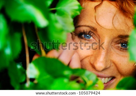Red-haired girl in the green foliage.