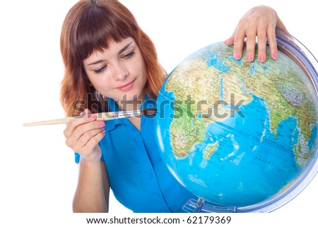 Red-haired girl is painting globe. Isolated on white background