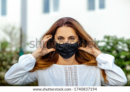 Red-haired girl putting on a black mask outside