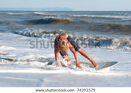 red-haired girl riding on the coastal waves on the surf