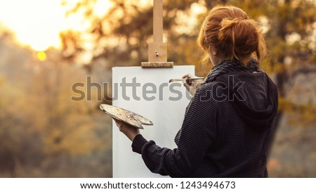red-haired girl with a bun painting a picture on an easel in nature, a young woman involved in creativity and enjoying beautiful landscape at sunset , concept of seasons mood and hobby