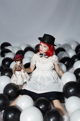Red-haired lady is sitting among black and white balloons and holding vintage doll in flowery dress with lace trimming, hat and pearl jewelry. Young woman is wearing lace dress and black hat.