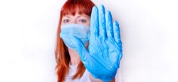 Red-haired middle-aged woman wearing a mask is holding her hand in a blue medical glove up against the camera. Stop the pandemic. Social distancing concept