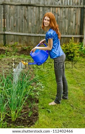 Red-haired smiling beautiful young woman in blue blouse bow waters from watering, against green of summer park.