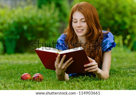 Red-haired smiling beautiful young woman in blue blouse lying on grass with book, against green of summer park.
