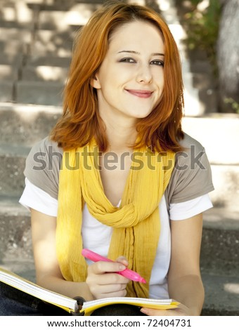 Red-haired student girl with notebook sitting at outdoor.