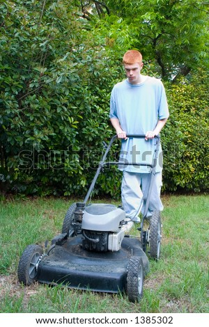 Red-haired teenaged young man mowing the lawn on a bright summer day.
