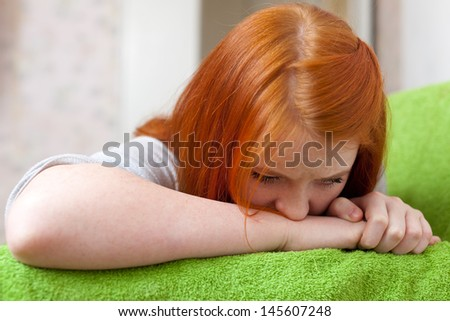 Red-haired  teenager girl  having disappointment in first love at home