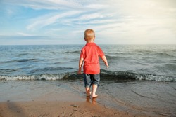 Red-haired toddler child kid in red t-shirt and jeans standing near water on lake sea ocean beach at evening sunset looking far away.  Happy lifestyle childhood concept. View from back.
