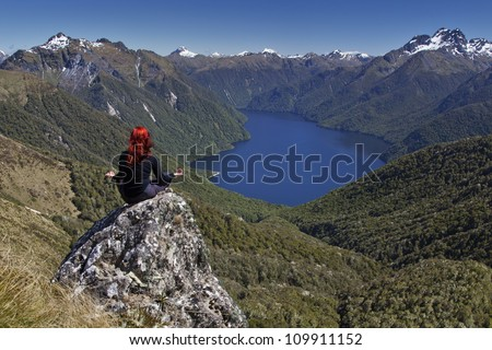 Red haired woman doing yoga overlooking lake and snow capped mountains.