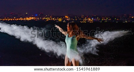 Red-haired woman in a blue bodysuit dancing in clouds of flour. A girl on the river bank jumping scattering white powder. #1545961889