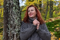 red-haired woman in a gray sweater in the autumn near a tree covered with moss