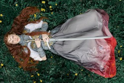 Red-haired woman in armor with a sword lies on the grass