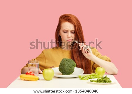 Red-haired woman in bad temper keeping strict vegetarian diet being tired of restrictions and hates greenery. Teenage girl holds broccoli on fork while making disgusting grimace, Foto d'archivio ©