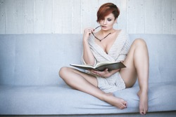 Red-haired woman in glasses reading a book