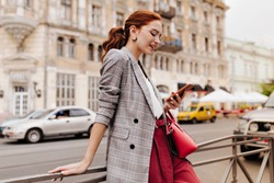 Red haired woman in stylish outfit chatting on phone