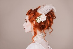 Red-haired woman in white dress with pale skin on gray background.  A vampire woman with a beautiful hairdo with a feather and flowers in her hair