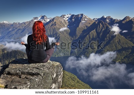 Red haired woman meditating in yoga position overlooking mountains and lake with white clouds.