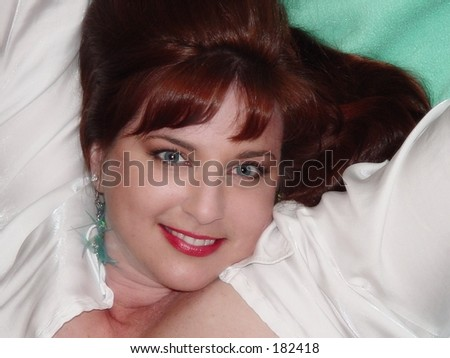 Red haired woman reclining in white satin shirt against green background