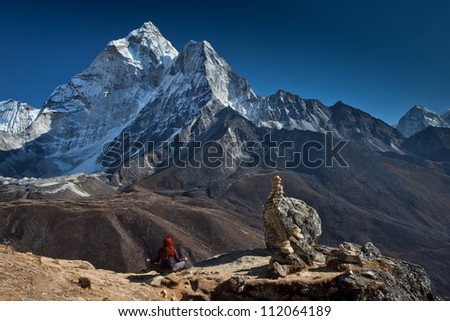 Red haired woman sitting in yoga position, meditating looking Ama Dablam and Himalayas in Nepal. - stock photo
