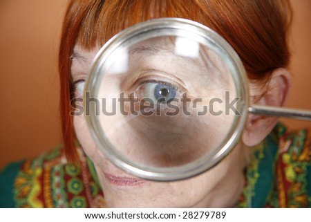Red haired woman with blue eye peering through a magnifying glass