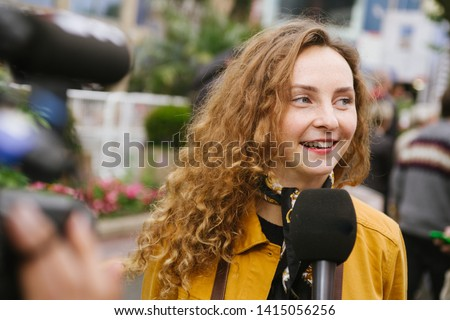 Red haired young teenager with hipster stylebeing interviewed by teelevision during a news event, right answer