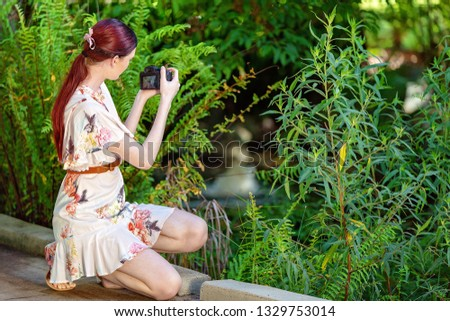Red haired young woman taking a photo of a pond in botanical gardens with a digital camera