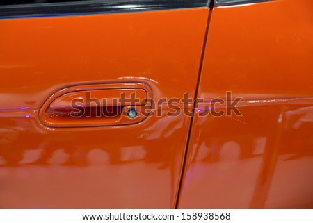 Red handle on the door of sports car