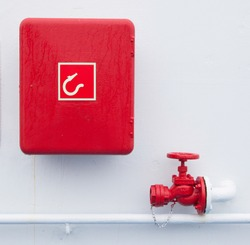 Red handled firehose outlet and a box with a firehose in it