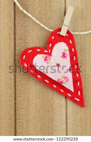 Red handmade felt heart clipped with a clothespin to clothes line on wooden background