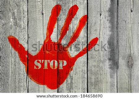Red handprint with the word ''Stop'' on old wooden fence background