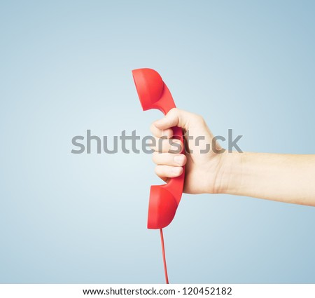 red handset in hand on blue background