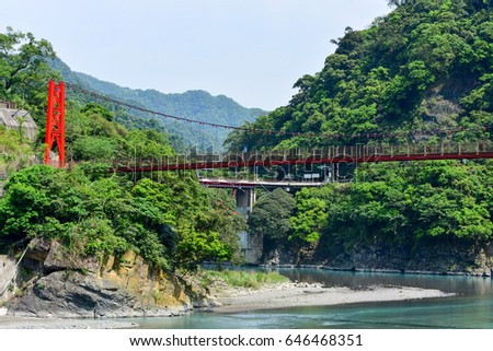 red hanging bridge or suspension bridge above the green river in the valley, Wulai, Taiwan #646468351
