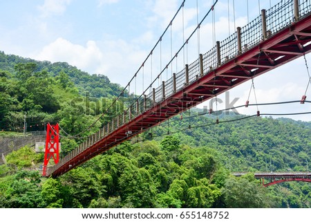 red hanging bridge or suspension bridge in the valley, Wulai, Taiwan #655148752