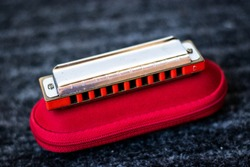 red harmonica music instrument on top of its case