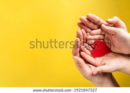 Red hart on palms of mother and son - Caucasian woman and child holding red hart shape above the modern abstract yellow background with copy space - Love care protection motherhood and family concept Stockfoto ©