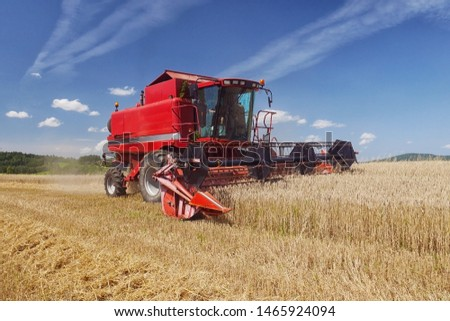 Red harvester harvesting grain on field, blue sky