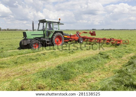 red hay turner behind tractor in green meadow in the netherlands