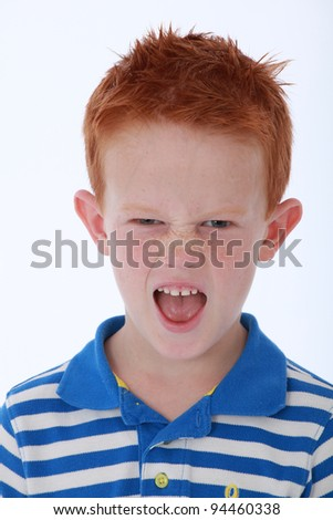 Red head boy wearing blue striped shirt with cheeky expression on face