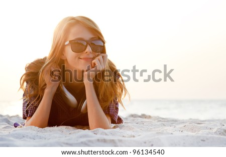 Red-head girl with headphones at the beach in sunrise.