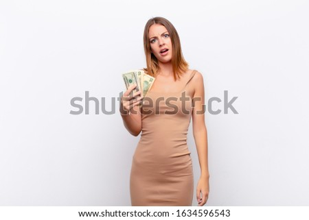 red head pretty woman feeling puzzled and confused, with a dumb, stunned expression looking at something unexpected with dollar banknotes