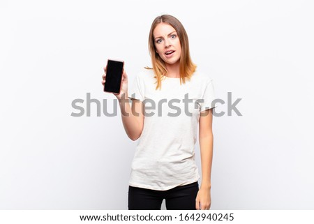 red head pretty woman feeling puzzled and confused, with a dumb, stunned expression looking at something unexpected holding a smartphone