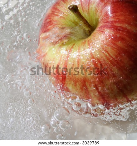 Red healthy apple in the water (close-up background). - stock photo