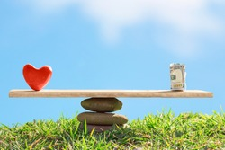 Red heart and dollar bills on the scales of stones and board on a blue sky background. The balance between love and money. Life or career. Family or career choice. Health care concept.