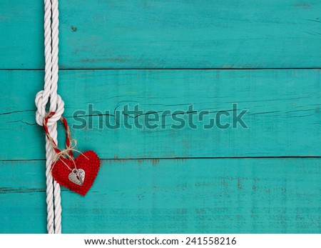 Red heart and silver lock hanging on white rope with knot border against blank antique teal blue rustic wooden background; Valentine's Day and nautical background with wood copy space