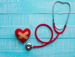 Red heart and stethoscope on blue bright wooden background. Healthcare and medical concept.