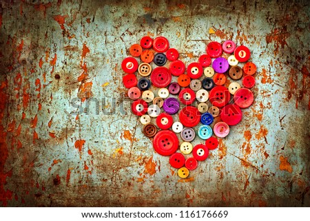 Red heart background on vintage old surface.Old colorful buttons/Valentines card with heart